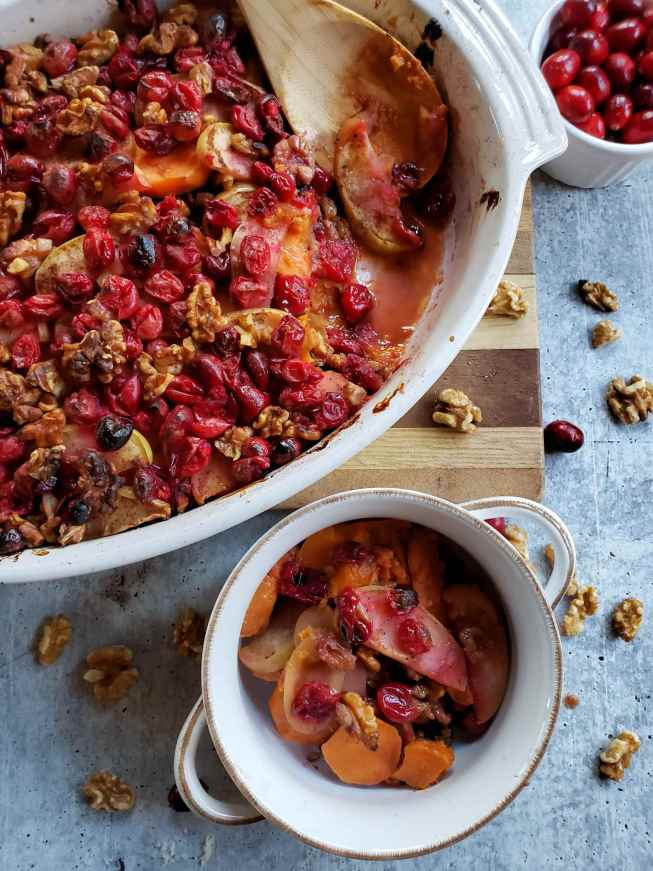 The yam apple cranberry walnut bake is shown in its baking dish after it has been baked. A serving is missing out of the dish and is now sitting in a smaller white bowl with two handles. A wooden spoon is resting in the baking dish and there is a light syrupy liquid remaining where the initial serving has been removed. The washed concrete surface underneath is littered with walnut pieces, cranberries, as well as a ramekin full of cranberries.
