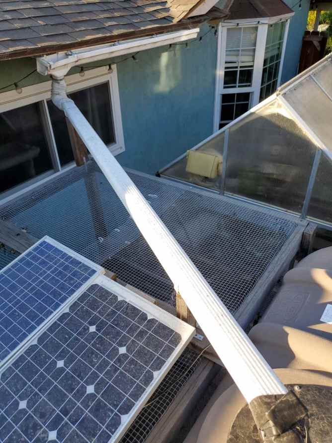 There are two solar panels sitting on top of the nearby chicken run. These are used to power the two fans inside the greenhouse next door. A large rain water tank can be seen directly next to the chicken run with a white pipe connected to the top of the tank. The white pipe helps collect rain runoff and then distributes it to the rainwater capture tank.