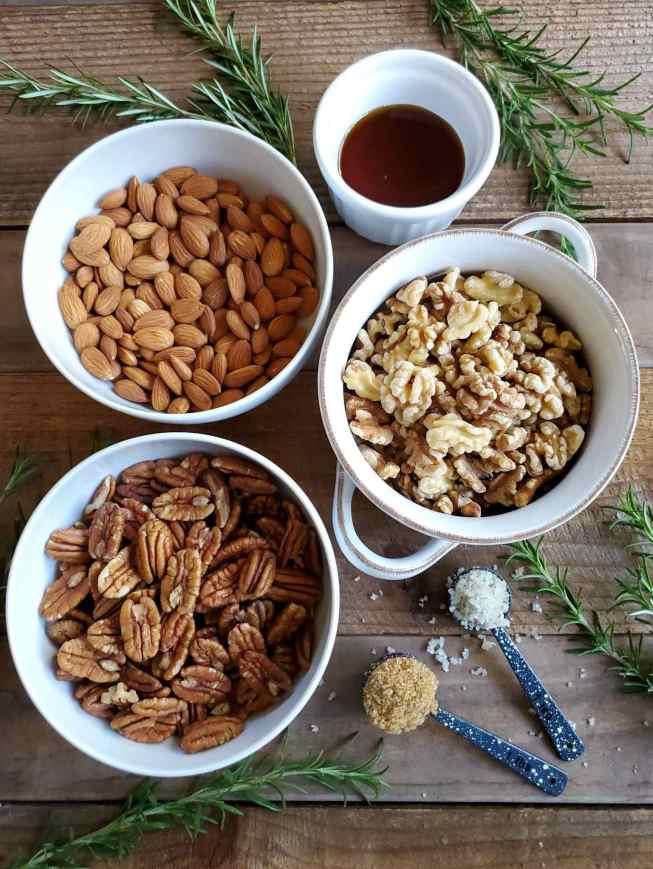 Есть три белые керамические миски одинакового размера: одна наполнена сырым миндалем, одна - сырыми грецкими орехами и одна - сырыми орехами пекан. Есть белая формочка меньшего размера, частично наполненная кленовым сиропом, и есть две разные мерки столовых ложек, одна коричневого сахара и одна, конечно, морская соль. Все они сидят на деревянной поверхности сарая со свежими веточками розмарина, разбросанными по изображению.