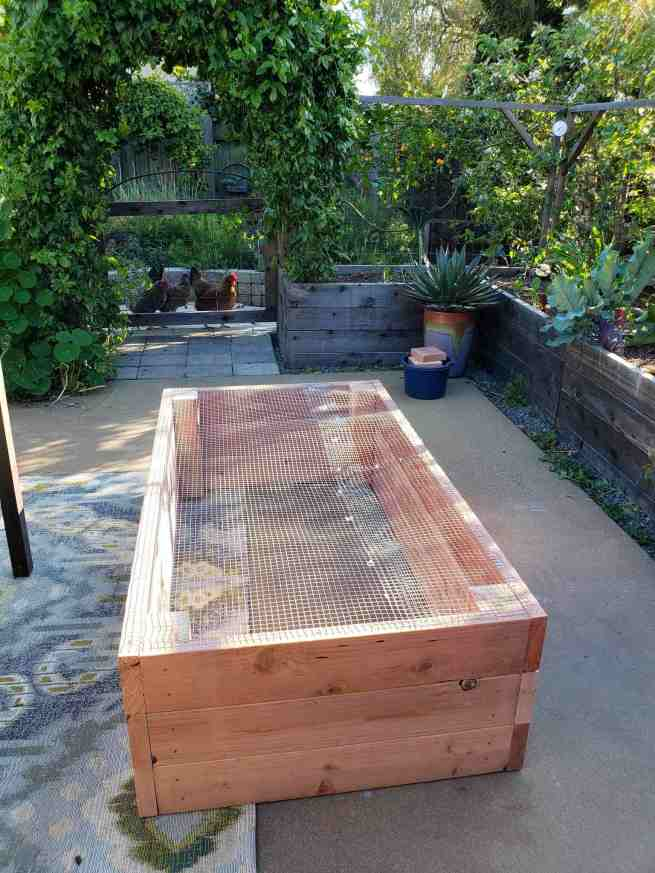 The bottom of a newly constructed raised garden bed is shown. It has been covered with hardware cloth which has been attached with screws. Another raised garden bed benefit is being able to protect your plants from below.