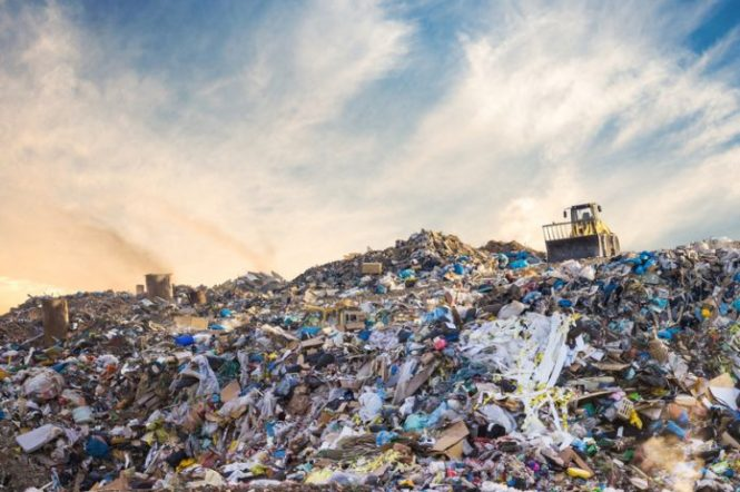 An image of a landfill with a tractor sitting on the top of the giant mountain of trash.