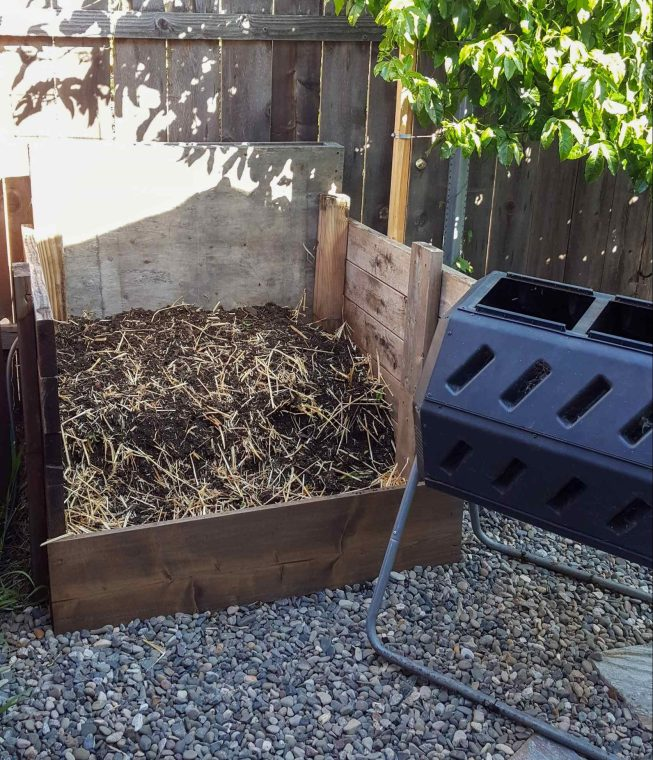 A three sided wooden compost stall is shown with a plastic compost tumbler staged next to it. The compost stall has some broken down material in it as well as some dried straw. These are  just two of the many options one can use to make compost.