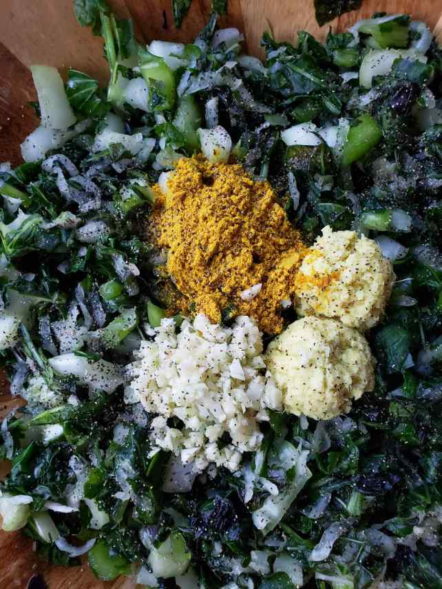 A close up image of chopped greens with two tablespoons of fresh ginger, one tablespoon of fresh garlic, one tablespoon of turmeric powder, and a sprinkle of black pepper  sitting neatly atop the greens.