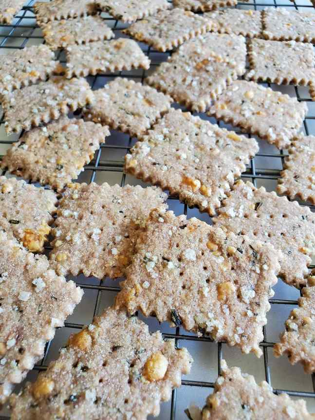 Gluten-free sourdough crackers spread across a wire cooling rack. Coarse sea salt is visible on the tops of the crackers as well has flakes of grated cheese that have turn a slight brown color from the oven. The edges of the. rackers are wavy from being cut with a pastry cutter.