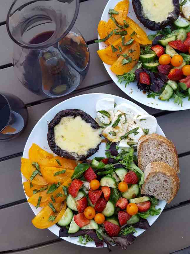 A mid summer dinner served on the outdoor patio table. There are two white ceramic dinner plates each one filled with fresh sliced yellow tomatoes, a green salad with Sungold tomatoes, cucumber, and strawberries, two slices of sourdough bread, slices of fresh mozzarella, and a grilled portabella mushroom with melted cheese. There is a carafe of red wine next to a stemless wine glass full of wine.