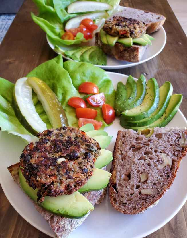 A small size homemade veggie burger is perched on top of 5 slices of avocado, splayed out on top of a thick slice of crusty sourdough bread. Next to the bread sits a leaf of lettuce with pickles and red tomato pieces on top.