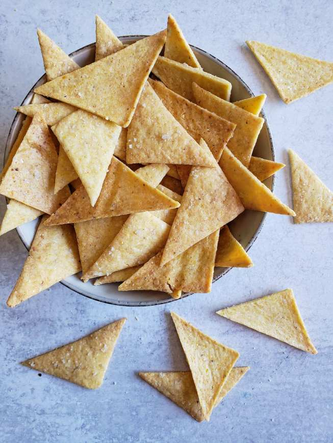 A close up image of a bowl of sourdough corn chips. They are golden to golden brown in color and triangular in shape. Specks of sea salt are visibly baked into the top of the chips. The bowl is overflowing with a few chips scattered around the perimeter of the bowl.
