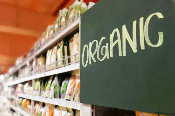 """A shelf of a grocery store is shown with a sign the reads """"ORGANIC"""" is featured, affixed to the grocery store shelf."""