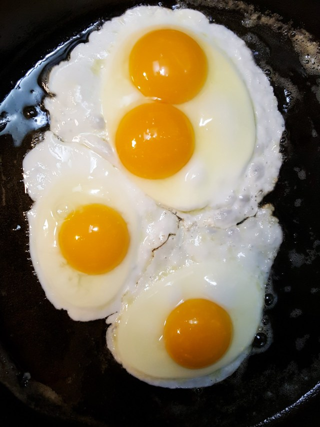 Four sunny side up or over easy eggs are being cooked in a cast iron skillet. The oil and edges of the eggs are visibly bubbling while the yolks and inner whites are not yet fully cooked.
