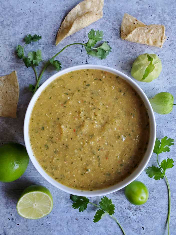 A white ceramic bowl full of roasted tomatillo salsa verde is featured. There are specks of cilantro, chili pepper, and seeds from the pepper visible. A whole lime, half a lime, fresh tomatillos, sprigs of cilantro and tortilla chips are scattered around the outside of the bowl.