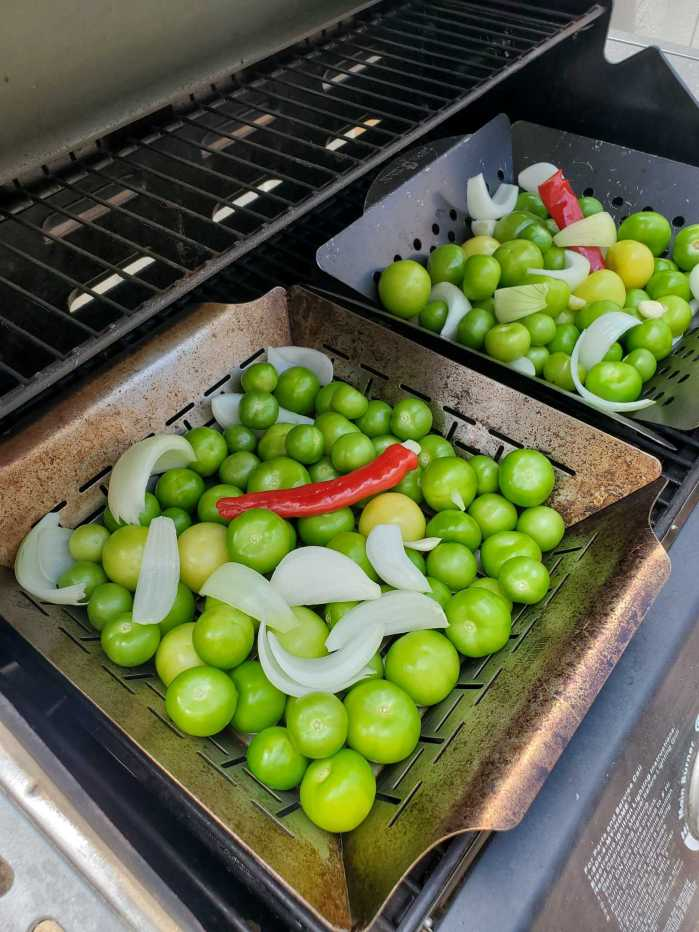The inside of a BBQ grill is shown with two stainless steel grilling baskets sitting atop the grill. Each basket is full of fresh tomatillos, quartered onions, garlic cloves, and a red chili pepper.