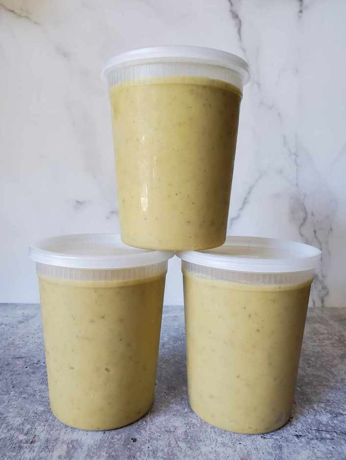 Three quart sized BPA free containers of potato leek soup and shown stacked in a semi pyramid. The soup is light beige in color.