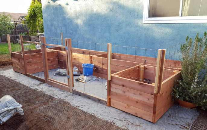 Four garden beds lined up against a house set in a U-shape. The beds are sitting on top of a layer of weed block fabric. There is fencing and a gate built into the front side of the garden beds where it would be open to chickens or other critters that is made with redwood 2x2's, 2x4's, and concrete remesh material.