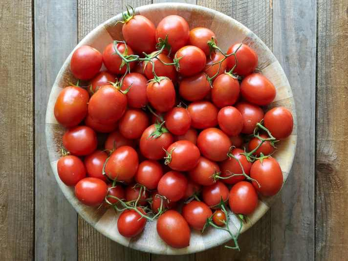 A large wooden bowl is shown full of Roma type tomatoes, some of them are attached in clusters. They are a beautiful red color, each with a slight sheen from the light.