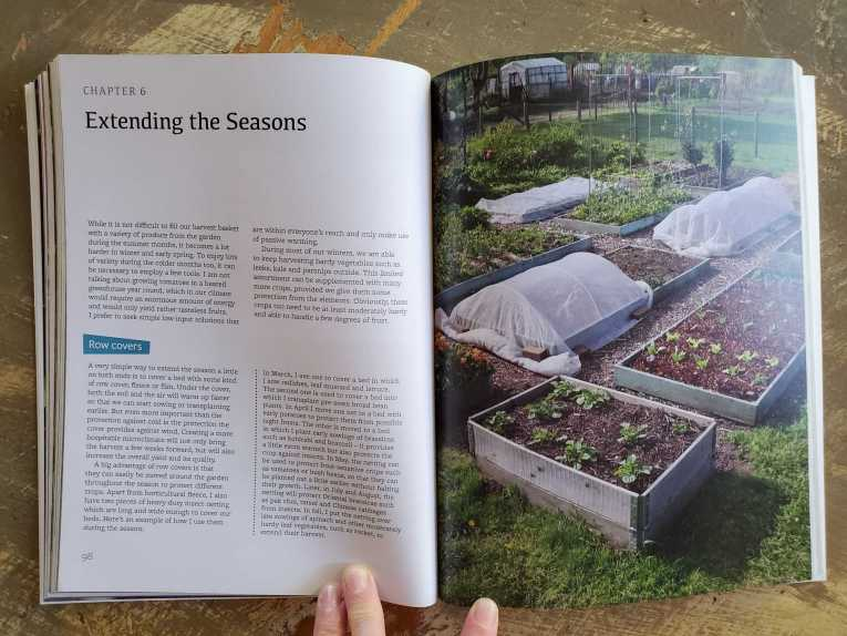 """A gardening book is open to a section about """"Extending the Seasons"""". One page is a full photograph of garden beds, some are left uncovered while others are covered in row covers, and some have wire trellises."""
