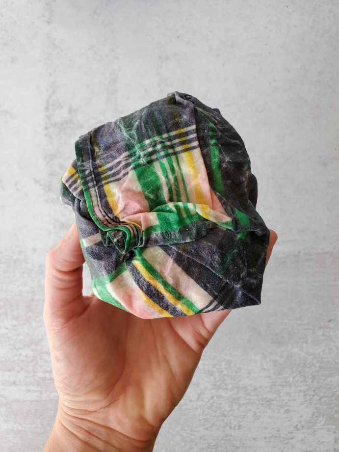 DeannaCat is holding a beeswax wrap that has been folded into a tight ball, half an apple is wrapped within.