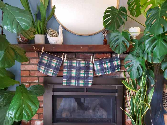 Three finished homemade beeswax wraps are hanging from a fireplace mantel. Each one is a different size from a small, to medium, and large size. Large houseplants are flanking each side of the mantel.