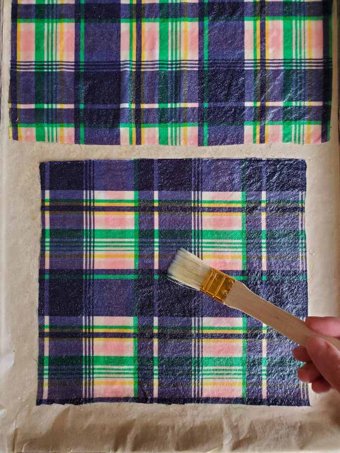 DeannaCat is using a paint brush to spread the melted beeswax to evenly and fully cover the fabric.