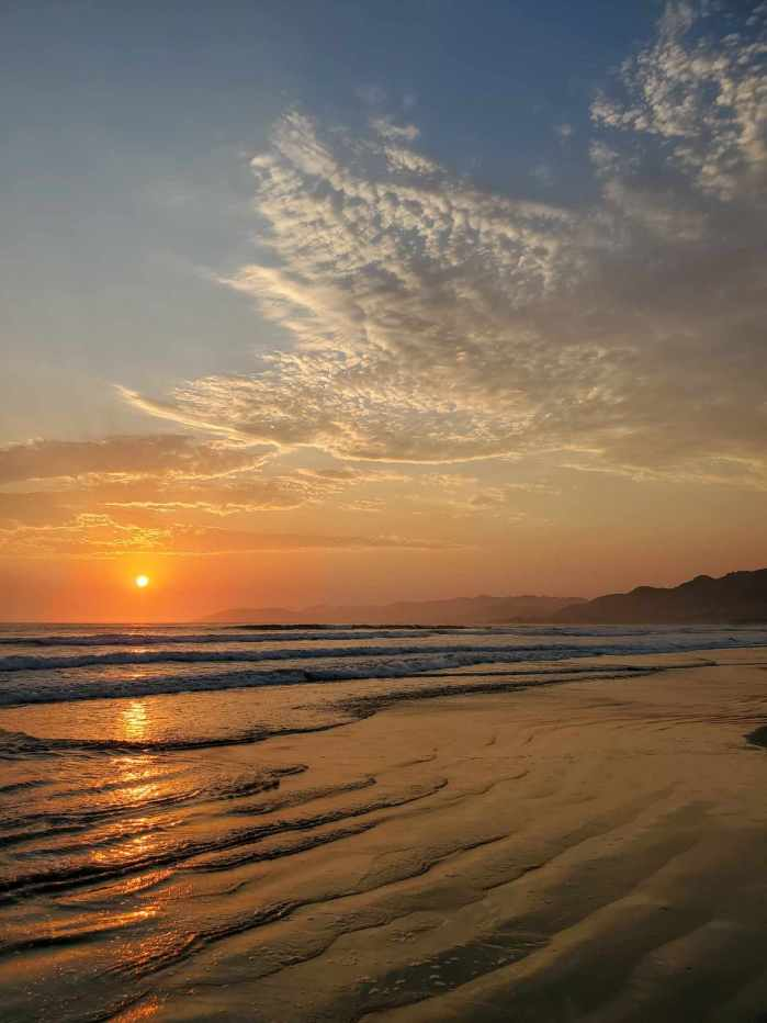 An image of the setting sun over the ocean, clouds collect in the sky of orange, blue, and purple. A walk admiring nature is a great way to reduce stress.