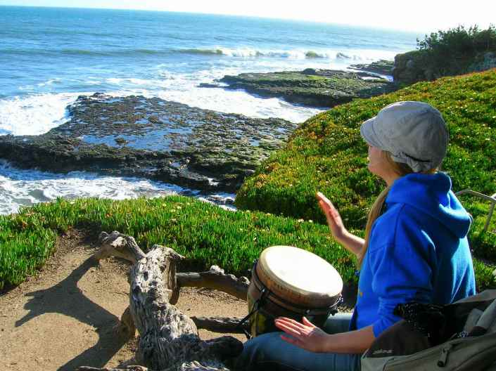 DeannaCat is playing a djembe hand drum on the ocean cliffs of Santa Cruz California. Her right hand is frozen in mid air on its way to the drums head. The blue ocean is crashing around rocky tidal outcroppings with ice pant surrounding the cliffside. Playing a musical instrument can help reduce stress.