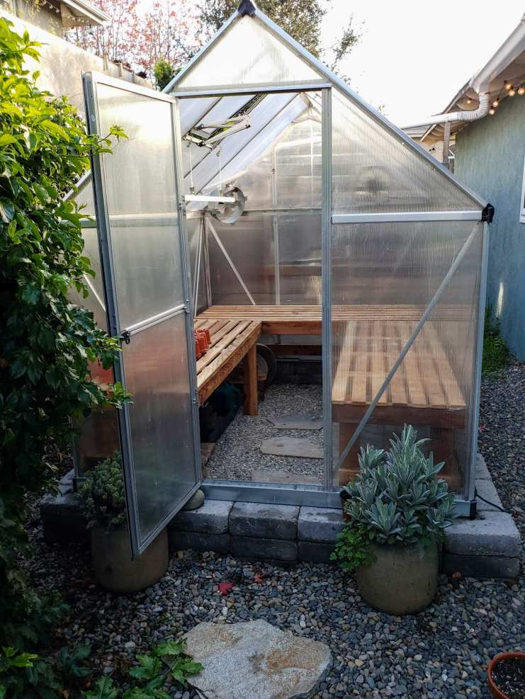 The greenhouse is shown from the outside. The three greenhouse benches line the inside walls in the shape of a U. Some smaller containers used for starting seeds are partially visible to the left of the inside of the greenhouse. Build a greenhouse bench to make the most of its space.