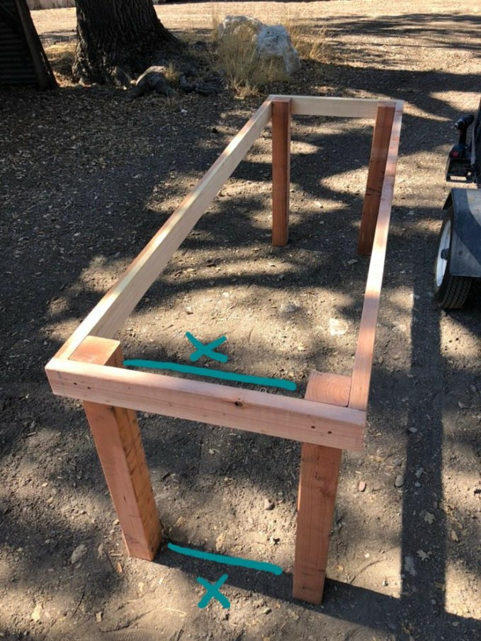 """A greenhouse bench partly constructed with four 4x4 legs and four 2x4 boards attached to the top ends of the 4x4's create a rectangular frame. An """"X"""" with a line showing the distance between the top of the 4x4's and the bottom of the 4x4's illustrates the even spacing."""