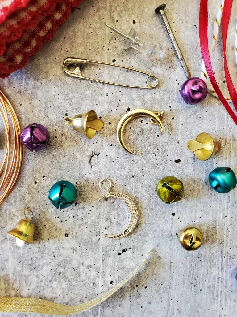 Trinkets and adornments that can be used to adorn an egg ornament. There are a variety of gold, purple, green and blue bells, crescent moon shapes of gold and crystals. At the top of the image there is a nail, thumb tack, and a safety pin. There is red and gold ribbon and copper wire bordering the image.