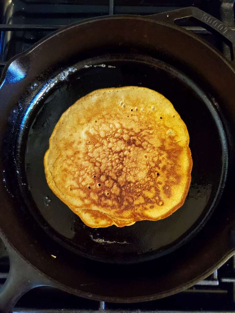 A birds eye view of the pancake after it has been flipped. The top of the pancake is golden brown with some remaining visible holes from the bubbles.