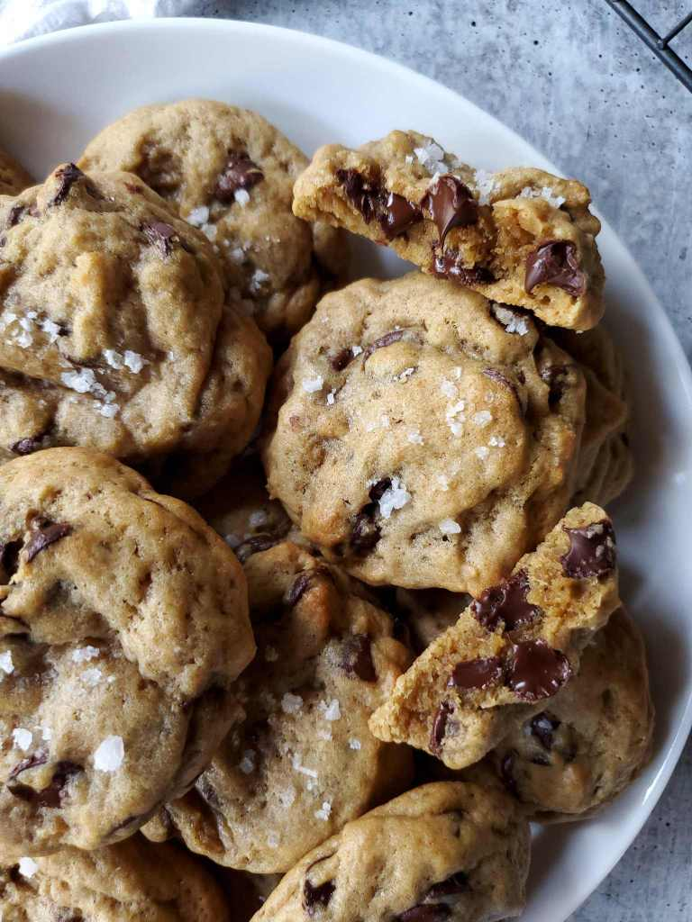A close up image of a white ceramic plate full of sourdough chocolate chip cookies. One of the cookies has be torn in half, revealing the gooey chocolate chips hiding within. The tops of the cookies have a sprinkle of flaky sea salt that has adhered to the cookie.