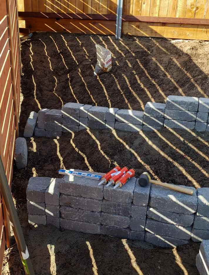 The process of building the stone terrace is underway, dirt is pulled away from each wall of the terrace while the pavers are glued together with strong adhesive.. The tubes of adhesive, a level, and a rubber mallet sit on the lowest formed stone terrace wall.