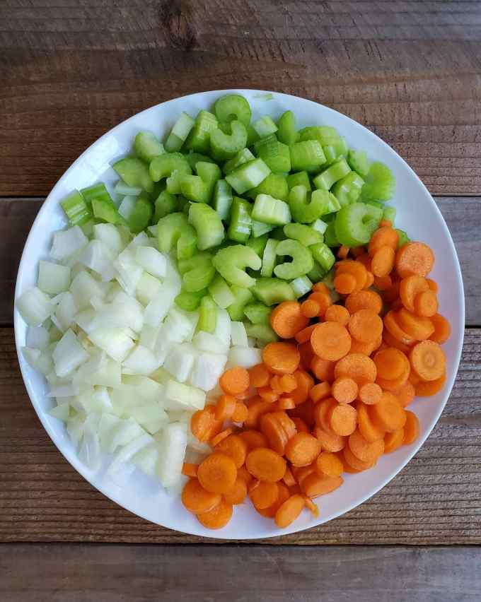 A white ceramic plate that is filled with 1/3rd chopped onion, 1/3rd chopped carrot, and 1/3rd chopped celery sit on a slatted wooden backdrop.