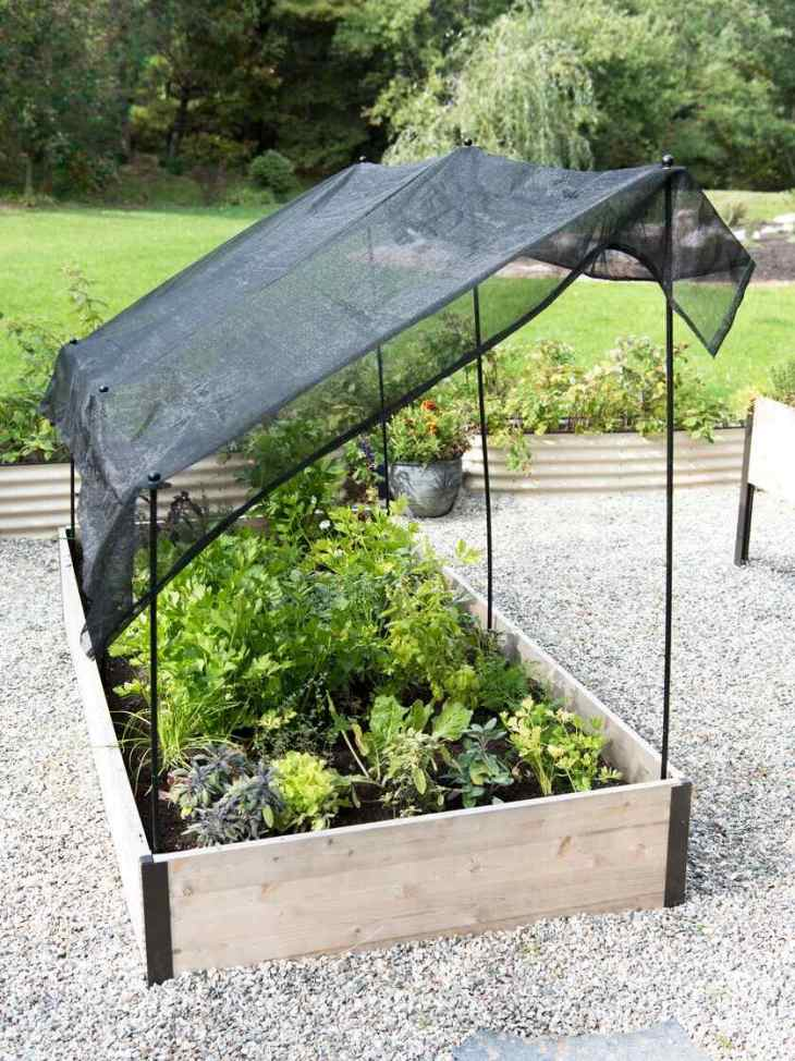 A raised garden bed sitting on a hardscape of gravel contains many types of herbs growing from parsley to sage. It is affixed with three black stakes on each sides of the length of the bed, a black piece of shade cloth is attached to the top of the stakes to create a lean-to of sorts to protect the plants from sunburn.