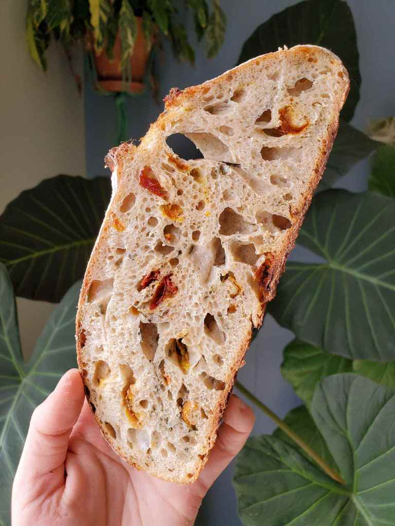 A slice of sourdough bread is featured with sun dried tomatoes and chopped rosemary. The bread is light brown in color with various holes throughout due to air pockets, dots of red and yellow with slivers of green are throughout the slice as well.