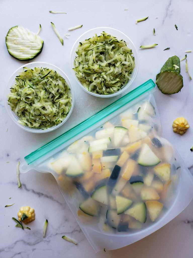 A flat lay image containing two 8 oz. BPA free containers full of shredded squash. Below lies the silicon bag full of squash chunks. Accenting the prepared squash are random grates of zucchini, slices of zucchini, as well as stem pieces from the squash.