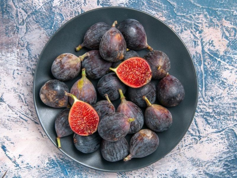 A slate grey plate is full of dark purple to black skinned figs with bright strawberry flesh inside. One of the figs is cut open in half to reveal the stunningly beautiful flesh.