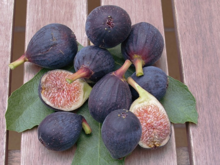 Medium sized dark purple fruit sit atop a leaf, one of the fruits is cut in half lengthwise, revealing the light strawberry colored pulp.