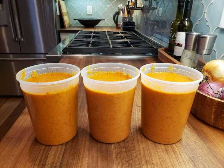 Three BPA free plastic quart jars sit on a butcher block countertop full of roasted tomato basil soup. A gas stove top is in the background with salt and pepper grinders, bottle of olive oil, along with red and yellow onions.