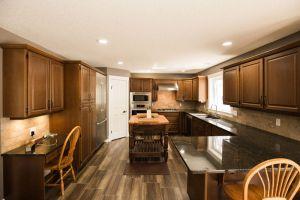 Homestead Custom Carpentry remodeled kitchen with dark wood, black granite countertops, and sleak design