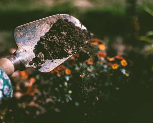 Person planting garden using garden tools to scatter soil
