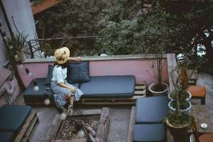 woman sitting on her outdoor furniture on her small deck