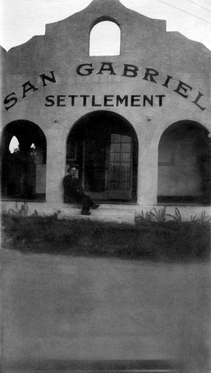 """A man sits on the front porch of a mission revival style building. Above, in painted letters, the building reads: """"San Gabriel Settlement."""""""