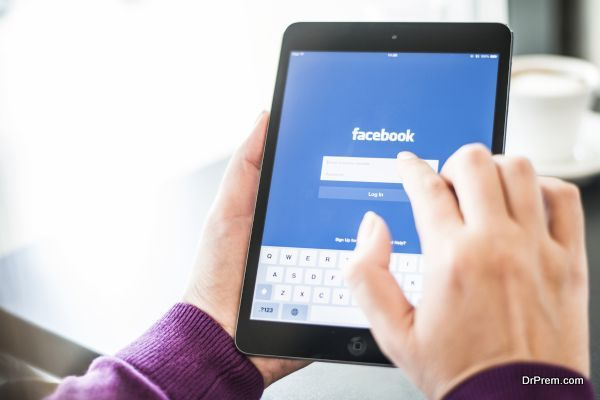 User holding an IPad with Facebook home page on screen