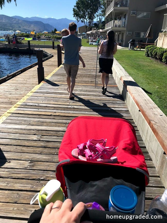 Best double stroller for travel 2019 - this picture shows the Joovy Caboose Ultralight Graphite rolling over a weathered boardwalk.