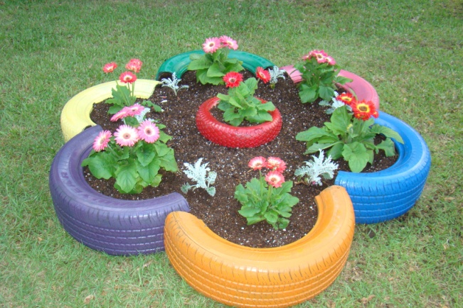 Flower bed made from old tires and small tire in the center. | Diy garden, Diy garden decor, Garden art