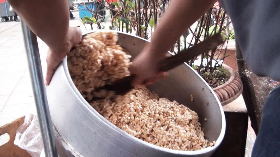 爆米香職人將麥芽糖拌入米香