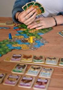 Spielsituation von El Dorado. Frau mit Karten in der Hand vor einer Kartenauslage