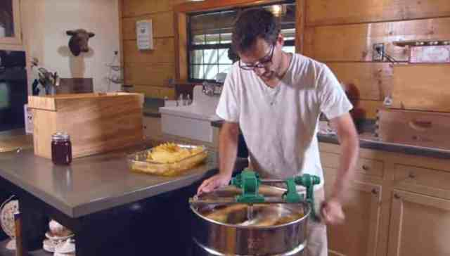 Man spinning a honey extractor with 4 frames inside
