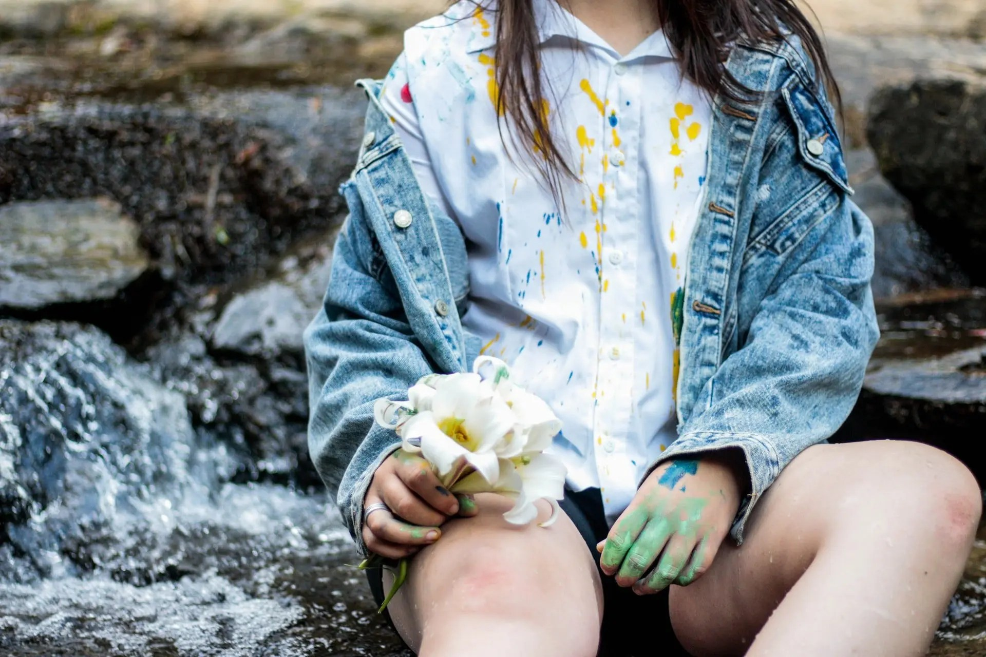 Girl covered in paint and holding flowers