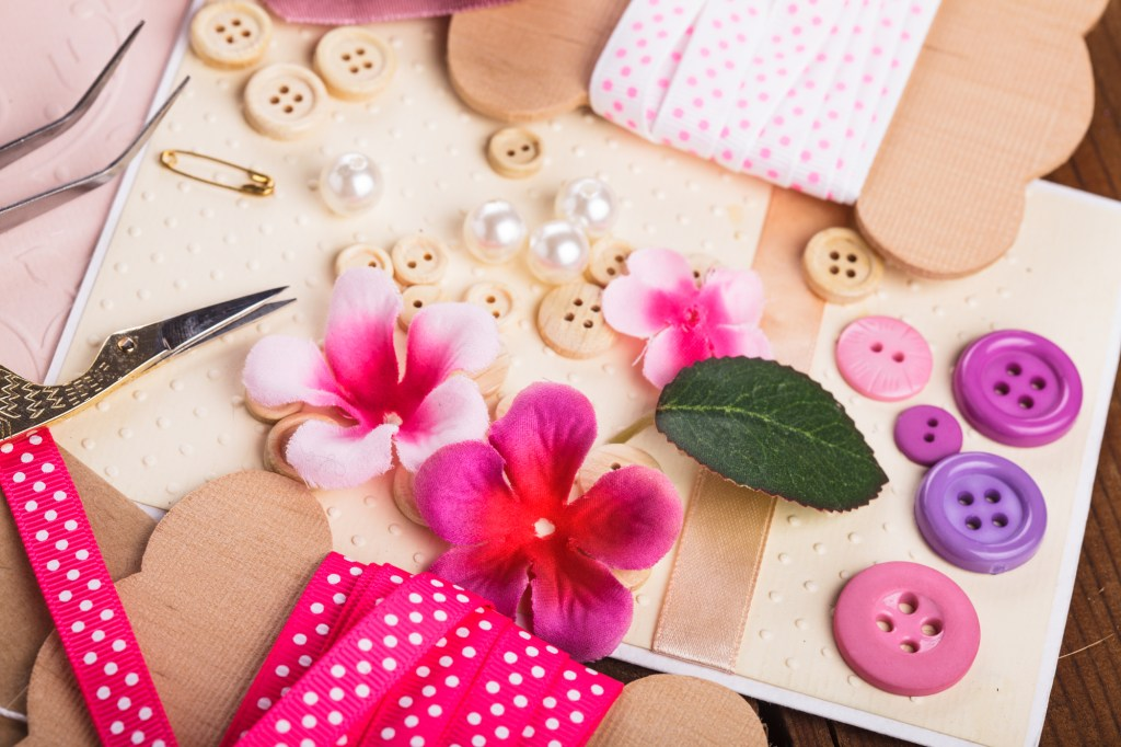 Colorful assortment of craft supplies including pink polka dot ribbon and silk flowers