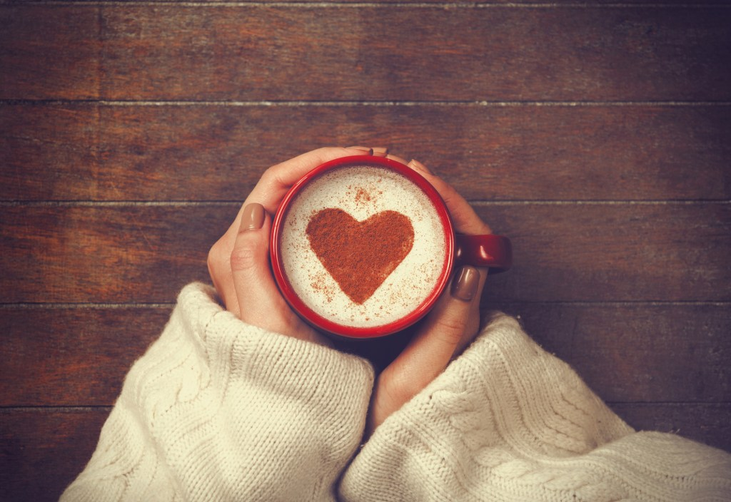 Woman holding espresso in mug with heart stenciled on the top